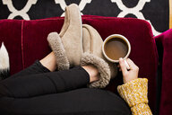 Low section of woman holding coffee cup while sitting on sofa at home - ASTF02890