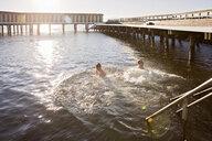 High angle view of father and son enjoying in sea by pier on sunny day - ASTF02896