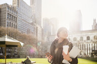 Businesswoman holding smart phone and laptop while waiting at Bryant Park - ASTF03052