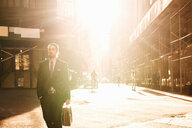 Businessman with briefcase walking on city street during sunny day - ASTF03076