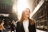 Smiling businesswoman standing on city street during sunny day - ASTF03082