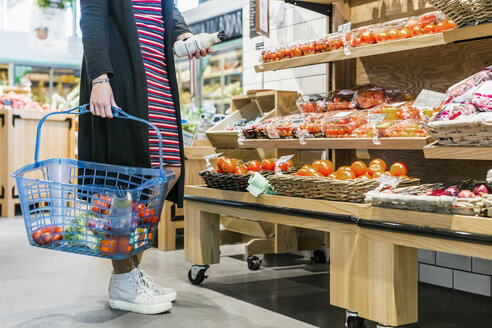 Low section of woman holding basket while shopping in supermarket - ASTF03205