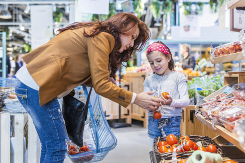Mother and daughter buying tomatoes in supermarket - ASTF03214