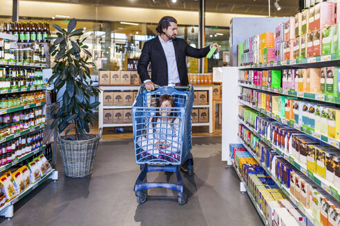 Girl sitting in cart while father shopping in supermarket - ASTF03226