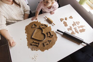 High angle view of mother and daughter preparing cookies at home - ASTF03247