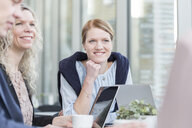 Happy businesswomen sitting in meeting at office - ASTF03337