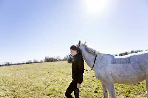 Side view of woman walking with horse on field against clear sky - ASTF03361