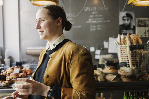 Side view of happy female customer holding coffee cup at cafe - ASTF03391