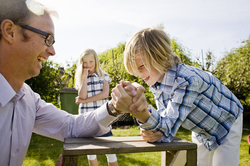 Girl looking at cheerful father arm wrestling with brother at back yard - ASTF03427
