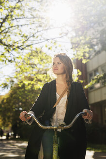 Beautiful young woman riding bicycle on city street - ASTF03565