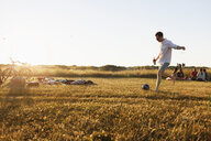 Man holding beer bottle while playing soccer at picnic - ASTF03586