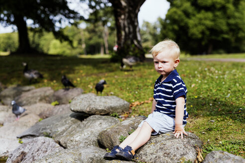 Full length of boy sitting on rock in park - ASTF03715