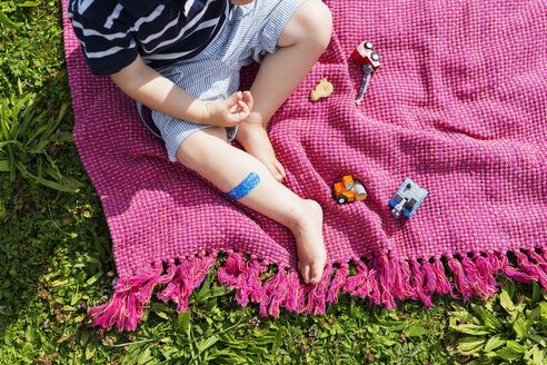 High angle low section of boy with toy cars on picnic blanket - ASTF03718