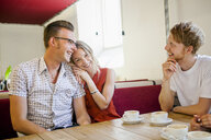 Happy couple with friend sitting at table in coffee shop - ASTF03748