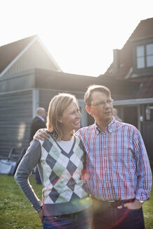 Man standing with arm around woman against house on sunny day - ASTF03784