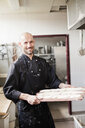 Portrait of confident male chef holding baguette dough on baking sheet in restaurant kitchen - ASTF03823
