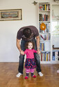 Cute girl walking with father on hardwood floor at home - ASTF03868