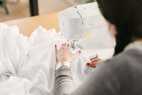 High angle view of female designer using sewing machine at studio - ASTF03886