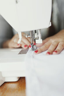 Cropped hands of fashion designer stitching fabric at studio - ASTF03889
