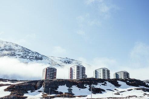 Low angle view of apartment buildings on snow covered mountain against sky - ASTF03925