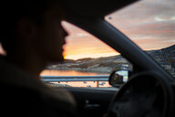 Young man driving car with sea view seen through window - ASTF03931