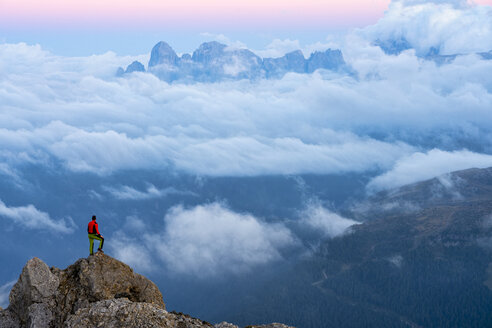 Italy, Veneto, Dolomites, Alta Via Bepi Zac, mountaineer standing on Pale di San Martino mountain at sunset - LOMF00826