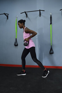 Woman practicing with kettlebell in a gym - ECPF00530