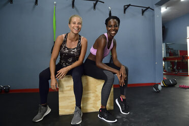 Portrait of two happy women sitting on a box in gym - ECPF00536