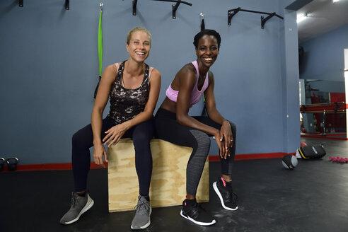 Portrait of two happy women sitting on a box in gym - ECPF00536