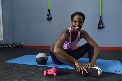 Portrait of happy woman sitting on a mat in a gym - ECPF00542
