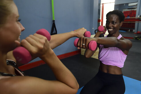 Two women doing fitness exercises with dumbbells in a gym - ECPF00545