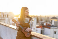 Young woman standing on roof terrace in the evening playing ukulele - AFVF02397