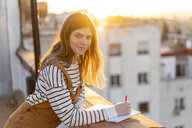 Portrait of young woman taking notes on roof terrace at sunset - AFVF02409