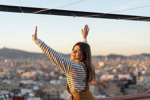 Portrait of happy young woman relaxing on roof terrace at sunset - AFVF02412