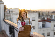 Portrait of smiling young woman gifting red lollipop on roof terrace at sunset - AFVF02418