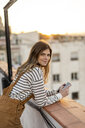 Portrait of smiling young woman with mobile phone relaxing on roof terrace at sunset - AFVF02421