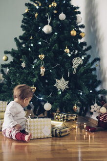 Baby girl sitting on the floor playing with Christmas gifts - MOMF00628