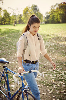 Young woman with bike in park - JHAF00038