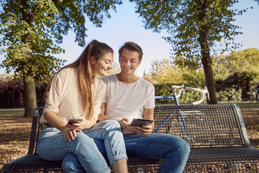 Young couple in park sitting on a bench with cell phone and tablet - JHAF00041