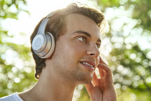 Smiling young man with headphones listening to music outside - JHAF00044
