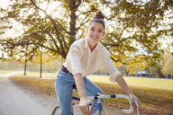 Portrait of smiling young woman riding bike at a park - JHAF00047