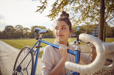 Young woman carrying bike at a park - JHAF00050