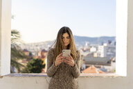 Serious young woman looking at cell phone - AFVF02432