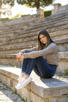 Portrait of young woman sitting on stairs outdoors - AFVF02438