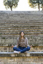 Young woman sitting outdoors on stairs doing yoga - AFVF02447