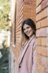 Portrait of a happy young woman at a brick building - AFVF02456
