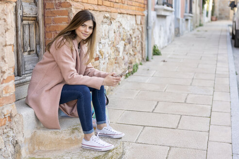 Portrait of a young woman sitting at house entrance holding cell phone - AFVF02459