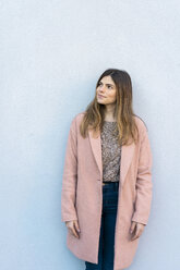 Young woman standing at a wall looking around - AFVF02462
