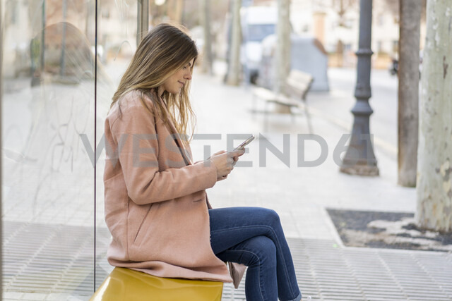 Young woman with cell phone waiting at bus stop - AFVF02465 - VITTA GALLERY/Westend61