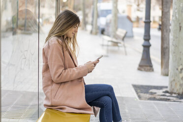 Young woman with cell phone waiting at bus stop - AFVF02465